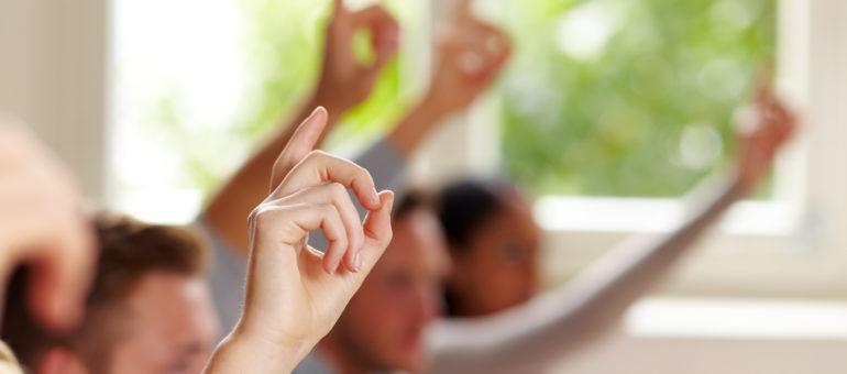 Erhobene Finger von Schülern im Unterricht